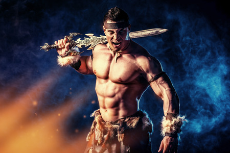 Portrait of a handsome muscular ancient warrior with a sword. photo