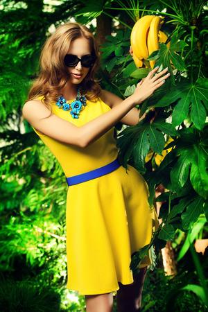Attractive young woman  among the tropical plants. Vacation. Tropics. Fashion shot. photo