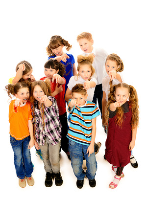 classmates: Group of joyful children shows a finger at the camera. Isolated over white. Stock Photo