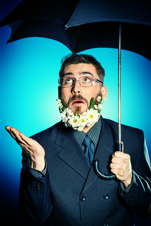 Extravagant businessman with a beard of flowers stands under his umbrella. photo