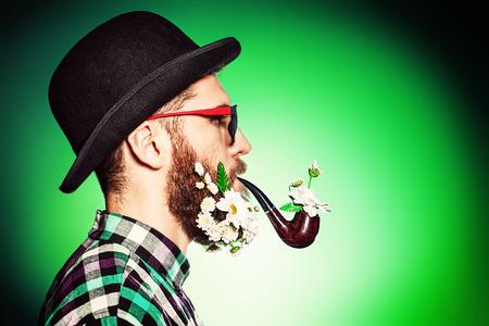 hombre fumando puro: Hombre extravagante, con una barba de flores vistiendo elegante bombín y fumando una pipa. Foto de archivo