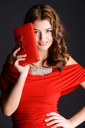 red purse: Stunning young woman with long curly hair looking at camera with beautiful smile. Fashion shot. Accessories. Black background. Stock Photo