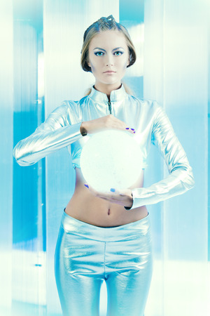 robot girl: Beautiful young woman in silver latex costume with futuristic hairstyle and make-up. Sci-fi style.