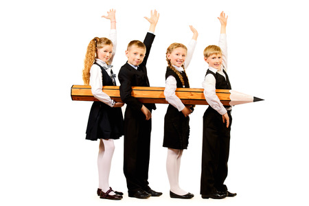 Cheerful schoolgirls and boys stand together and hold a huge pencil. Educational concept. Isolated over white. photo