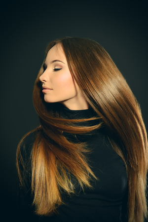 flying hair: Beautiful girl with magnificent long hair in motion posing over black background. Stock Photo