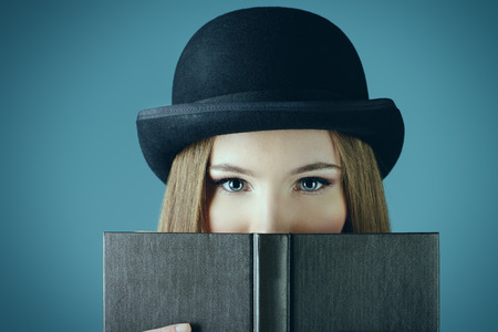bookworm: Close-up portrait of the elegant girl model in bowler hat reading a book. Refined style of old Europe.
