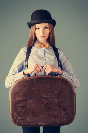 Portrait of the elegant girl model in bowler hat holding her old suitcase. Refined style of old Europe.  photo