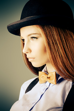 Elegant girl model poses in blouse, bow tie and bowler hat. Refined style of old Europe. Sepia. photo