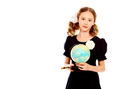 Portrait of a ten years schoolgirl uniform holding a globe. Isolated over white.