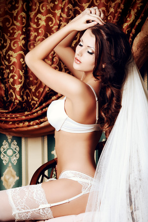 Attractive young woman alluring in sexual white lingerie and bridal veil. photo