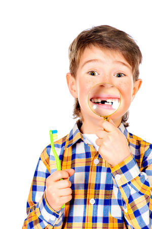 Little funny boy smiling through a magnifying glass, showing his teeth. Healthcare. Isolated over white. photo