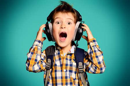 persona cantando: Lindo niño de 7 años de escuchar música en los auriculares. Foto de archivo