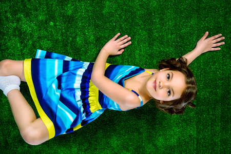 7 years old: Beautiful smiling girl in bright summer dress lying on a grass.  Stock Photo