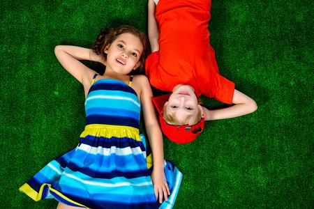 ropa de verano: Feliz niña sonriente y muchacho en ropa de verano brillante acostado en una hierba. Niños.