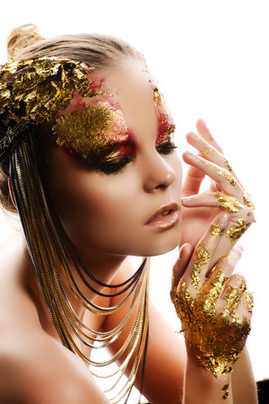 glitter makeup: Art project: beautiful woman with golden make-up. Jewelry, make-up. Fashion. Isolated over white.