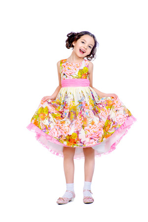 7 years old: Pretty smiling girl in a beautiful summer dress. Isolated over white.