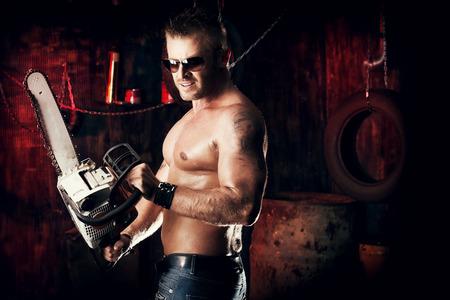 violence in the workplace: Hombre musculoso guapo expresivo con una motosierra en el antiguo garaje. Foto de archivo