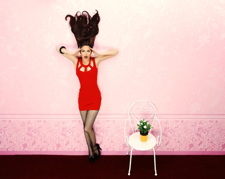 fashion shopping: Fabulous young woman with flying up hair standing in a pink room.