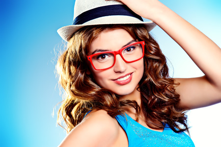 Pretty cheerful woman in hat and glasses smiling at the camera.  photo