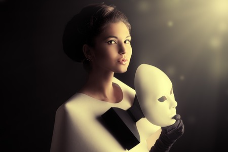 Art fashion photo of a gorgeous woman in paper dress holding theatrical mask. Black and white. photo