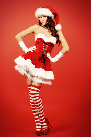 Full length portrait of an attractive young woman in Santa Claus costume over red background. Christmas. photo