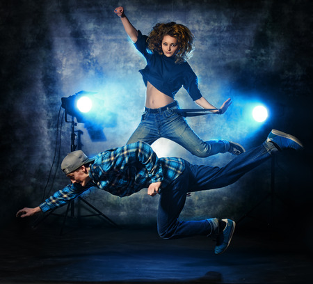 breakdance: Two modern dancers jumping over grunge background. Hip-hop. Urban, disco style. Stock Photo