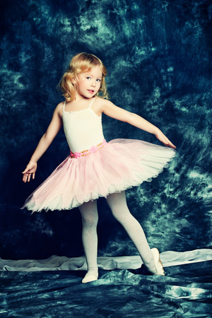Pretty little girl ballerina in tutu posing over vintage background. photo