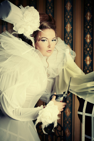 Beautiful fashion model in the refined white dress and mannequin. Vintage style. Art project. Haute Couture. photo