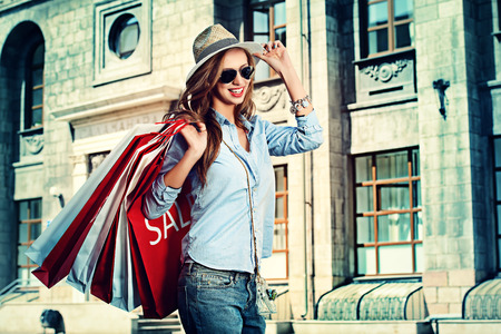 stylish girl: Beautiful happy girl goes shopping in the city.