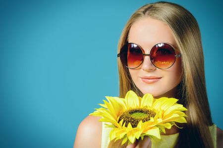 brigt: Beautiful summer girl in brigt yellow dress and sunglasses stands with a sunflower.