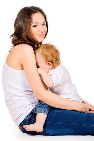 lactancia materna: Madre feliz con su pequeño bebé. Aislado en blanco. Foto de archivo