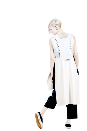 Full length portrait of an extravagant model with boyish make-up and haircut. Isolated over white.