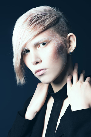 Fashion photo of an extravagant model over black background. Hairstyle, make-up. Stock Photo