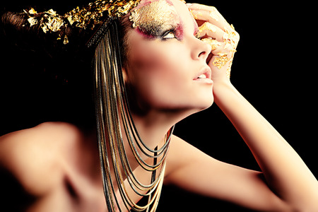 Art project: beautiful woman with golden make-up. Jewelry, make-up. Fashion. Over black background. photo