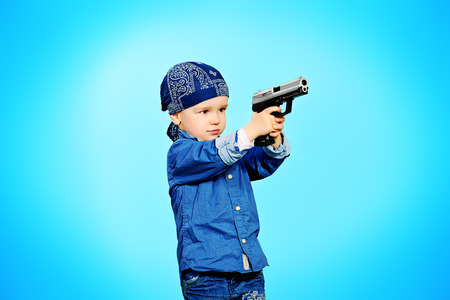 2 year old: Cute 2 year old boy playing with a gun over blue background. Childhood.
