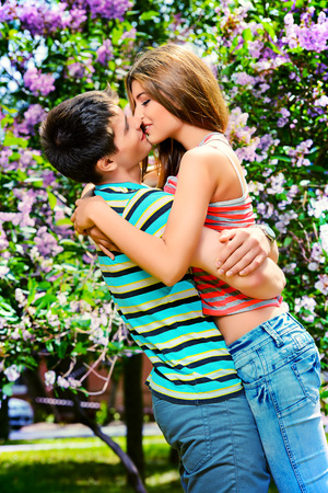 Romantic young people tenderly kissing outdoor. Love concept. photo