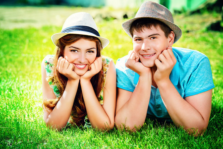 Happy young couple relaxing on the lawn in a summer park. Love concept. Vacation. photo