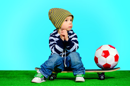 Cute two year boy sitting on a skateboard with a ball. Fashion. Childhood. photo