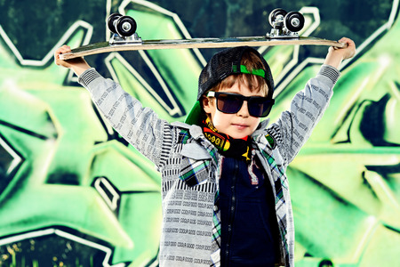 skater boy: Cool 7 year old boy with his skateboard on the street. Graffiti background. Childhood. Summertime.