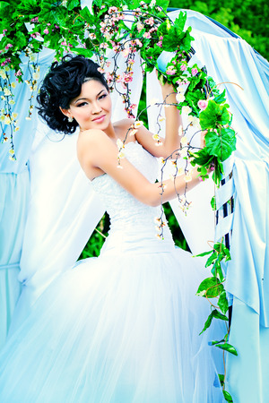 Beautiful elegant asian bride stands under the wedding arch. Wedding dress and accessories. Wedding decoration.  photo