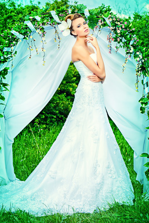 Beautiful elegant bride stands under the wedding arch. Wedding dress and accessories. Wedding decoration.  photo