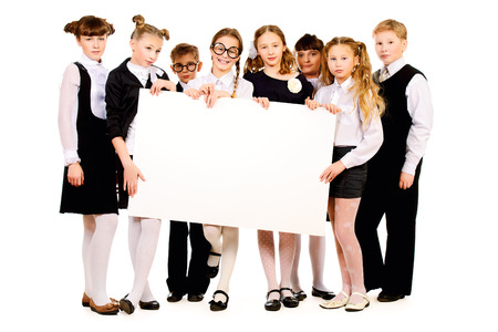 Group of schoolchildren standing together and holding white billboard  Copy space  Isolated over white  photo