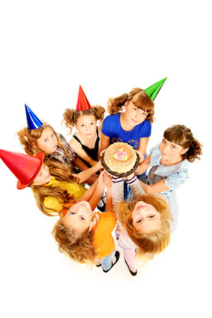 Group of happy kids celebrating birthday with a cake  Isolated over white  photo