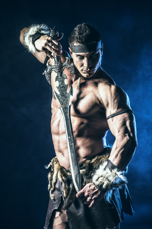 barbarian: Portrait of a handsome muscular ancient warrior with a sword.
