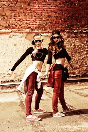 persone che ballano: Ballerini di hip-hop moderno sopra il muro di mattoni. Stile di vita urbano.