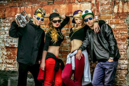 hip hop man: Group of young modern people posing together with fun. Urban lifestyle. Hip-hop generation.