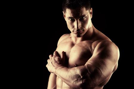 male torso: Handsome muscular bodybuilder posing over black background.