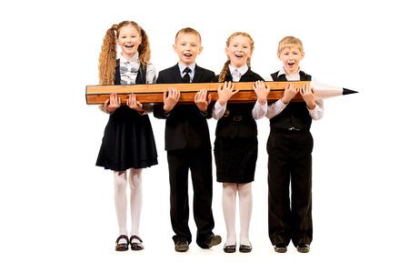 uniform school: Colegialas alegres y los ni�os est�n juntos y tienen un gran l�piz. Concepto educativo. Aislado en blanco.