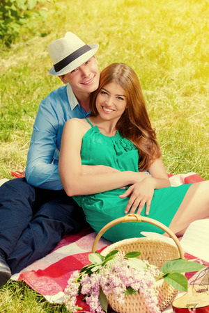 man woman hugging: Happy young couple relaxing on the lawn in a summer park. Love concept. Vacation. Stock Photo