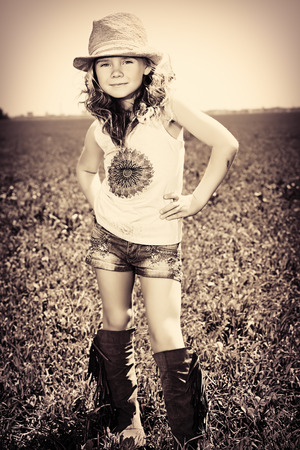 Pretty little girl on a meadow in summer day. Happy childhood. Wild west style, jeans. photo